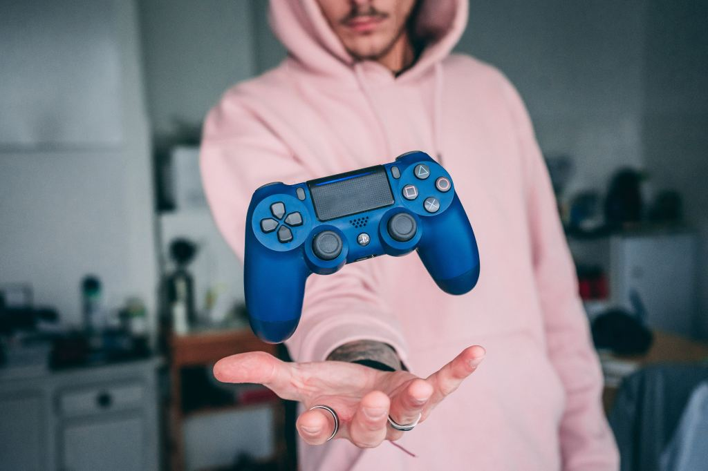 Guy wearing pink sweater tossing blue Playstation 3 controller in the air