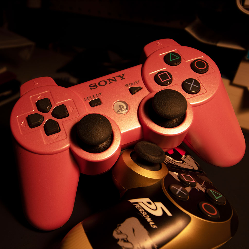 Pink Playstation 3 controller and gold Playstation 4 controller