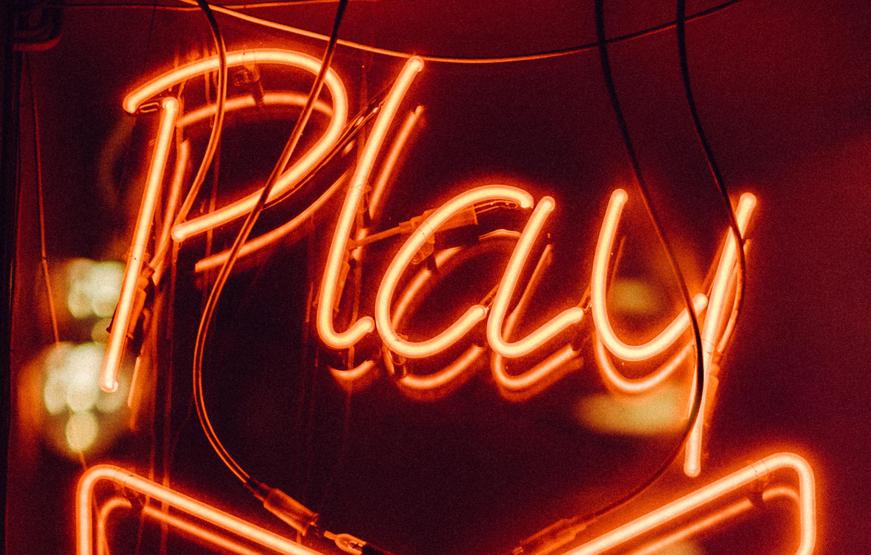 """Neon orange """"Play"""" sign"""