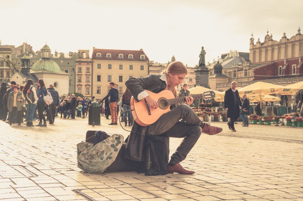 Musician playing guitar in town square