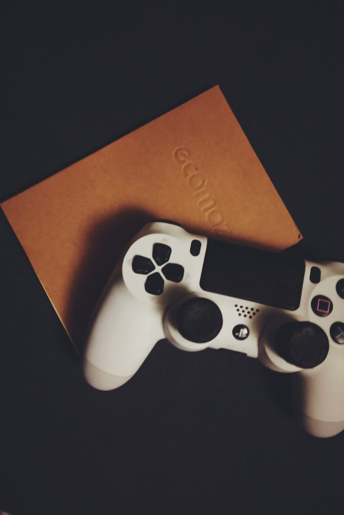 White Playstation 4 controller on top of journal
